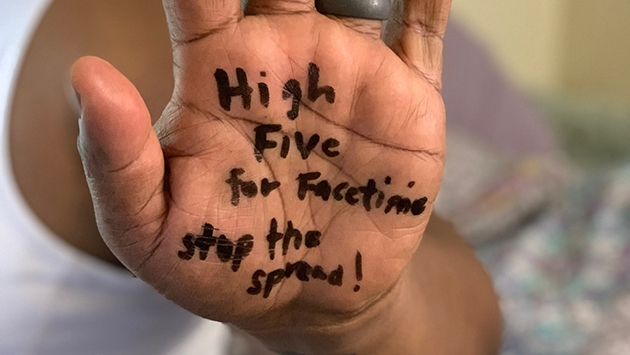 A young person holding up a virtual high 5 to encourage social distancing but not social disconnection.